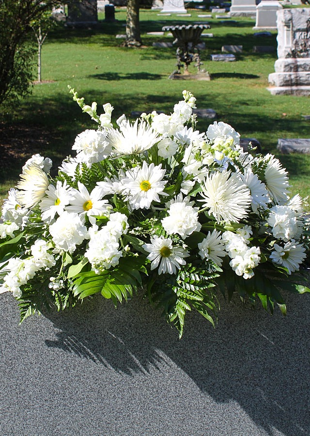 Display of All White Cemetery Saddle by The Flower Alley